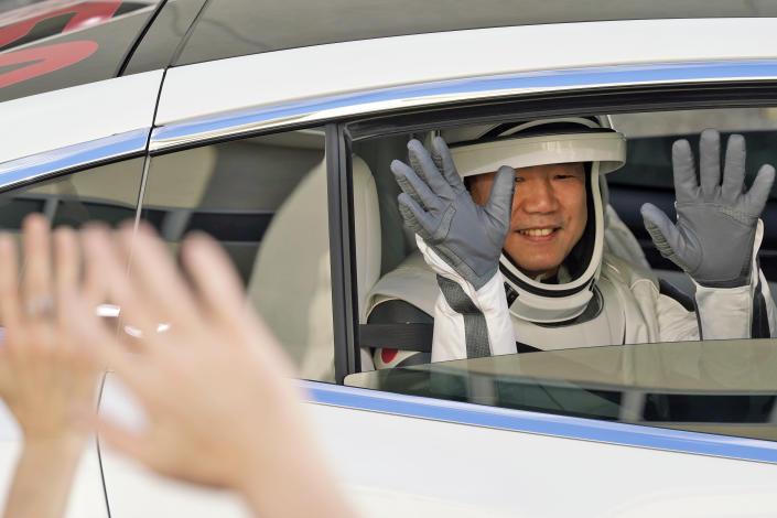 Japan Aerospace Exploration Agency astronaut Soichi Noguchi waves to family members as he leaves the Operations and Checkout Building with fellow crew members for a trip to Launch Pad 39-A and planned liftoff on a SpaceX Falcon 9 rocket with the Crew Dragon capsule on a six-month mission to the International Space Station Sunday, Nov. 15, 2020, at the Kennedy Space Center in Cape Canaveral, Fla. (AP Photo/John Raoux)