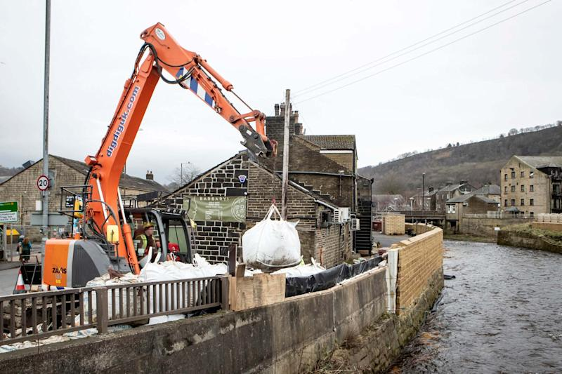 Flood defences are put up in the Upper Calder Valley in West Yorkshire (PA)