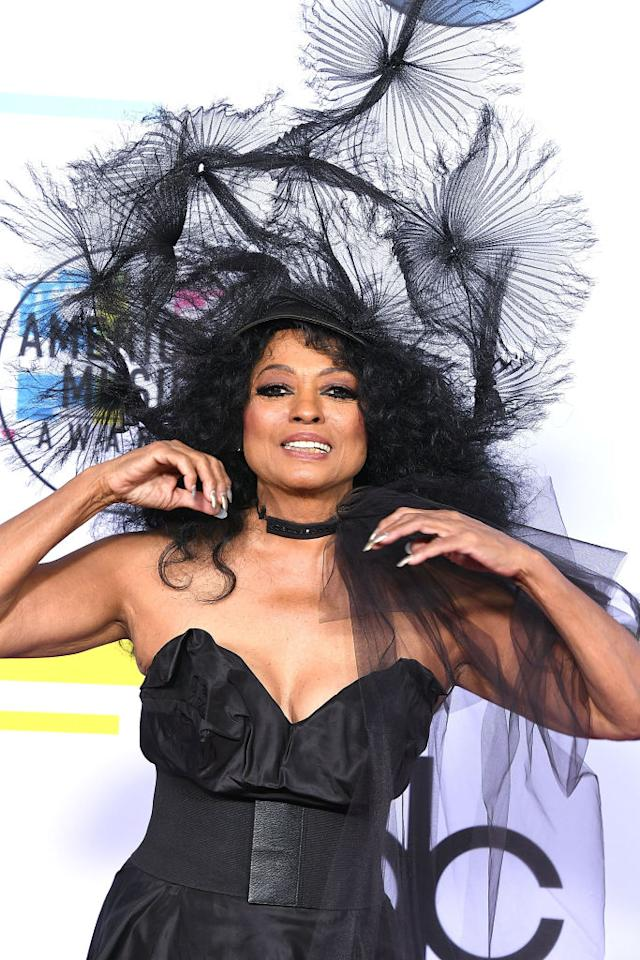 <p>The stunning 73-year-old walked the red carpet in a webbed black fascinator and plunging shoulderless gown, before accepting the AMA's Lifetime Achievement Award that night. <i>(Image via Getty)</i> </p>