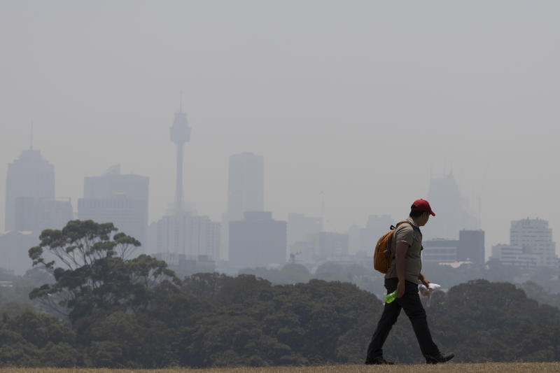 Smoke blankets the Sydney CBD as a man walks by in a cap and jeans.