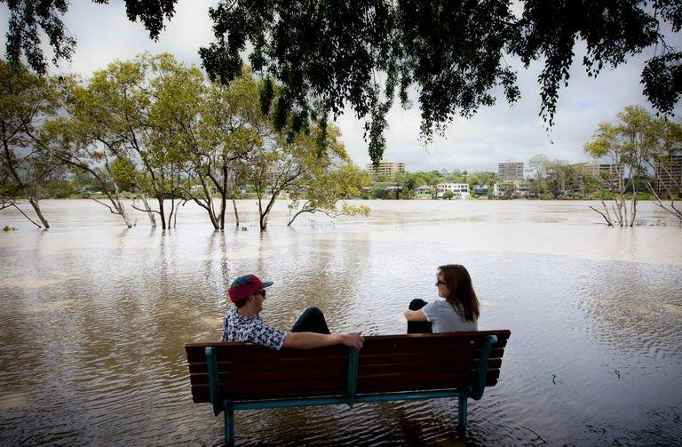 Two people sit on a bench surrounded by floodwaters at West End in Brisbane on January 28, 2013