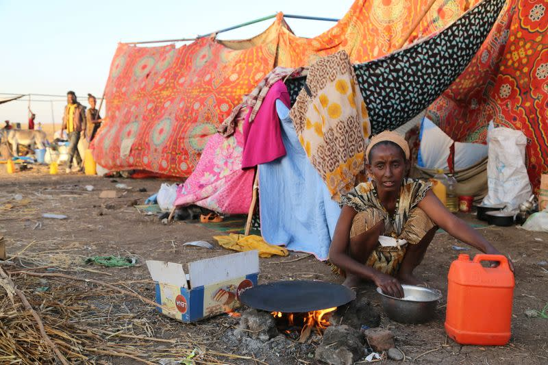 An Ethiopian who fled the ongoing fighting in Tigray region, prepares a meal before being processed for emergency food and logistics support by the WFP in Hamdait village on the Sudan-Ethiopia border in eastern Kassala state