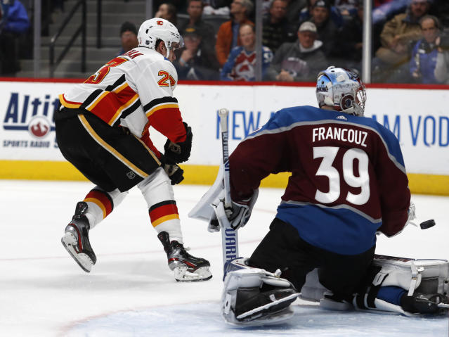 The winning goal shot by Calgary Flames center Sean Monahan, left, flies past Colorado Avalanche goaltender Pavel Francouz into the net in overtime of an NHL hockey game Monday, Dec. 9, 2019, in Denver. The Flames won 5-4 in overtime. (AP Photo/David Zalubowski)