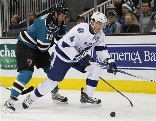 Tampa Bay Lightning center Vincent Lecavalier (4) vies for the puck against San Jose Sharks center Joe Thornton (19) during the first period of an NHL hockey game in San Jose, Calif., Wednesday, Dec. 21, 2011. (AP Photo/Tony Avelar)