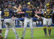 Milwaukee Brewers starting pitcher Corbin Burnes (39) greets relief pitcher Josh Hader as Omar Narvaez watches at the end of a baseball game against the Cleveland Indians in Cleveland, Saturday, Sept. 11, 2021. Hader and Burnes combined for a no-hitter. (AP Photo/Phil Long)