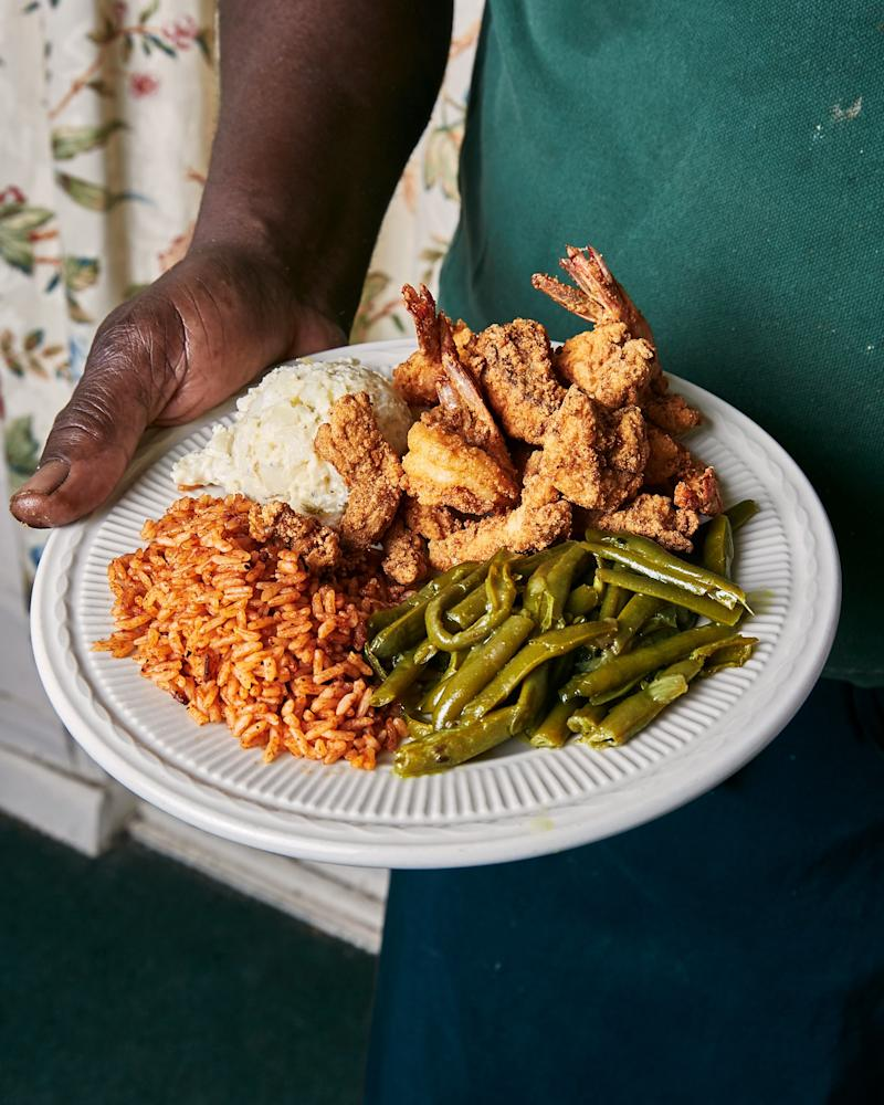 Owner Bill Green serves up a few of his specialties: fried shrimp, fried shark, green beans, red rice and potato salad.