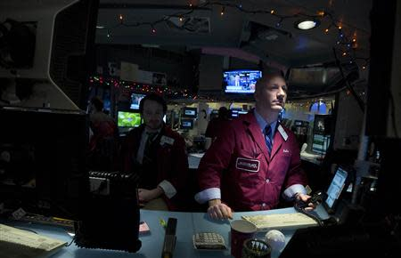 Traders work on the floor of the New York Stock Exchange after the opening bell in New York, December 24, 2013. REUTERS/Carlo Allegri