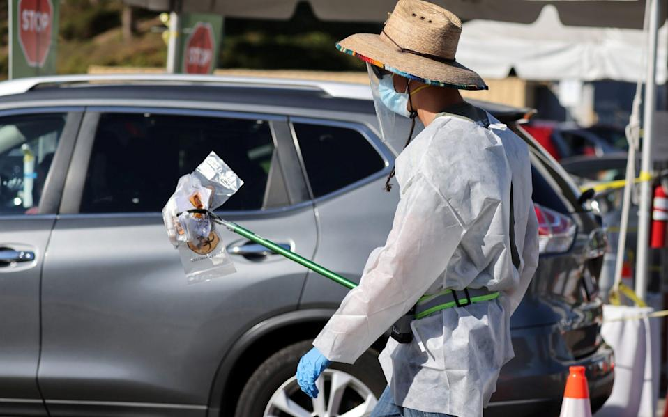 A worker carries novel coronavirus tests at a testing site in Los Angeles - LUCY NICHOLSON/REUTERS
