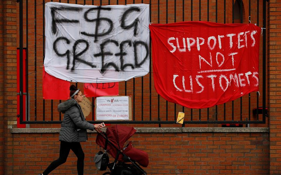A woman walks past protest banners hung outside Anfield - PHIL NOBLE /Reuters