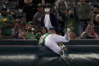 Oakland Athletics' Matt Chapman dives for a foul ball hit by Seattle Mariners' Jake Bauers during the fourth inning of a baseball game in Oakland, Calif., Tuesday, Sept. 21, 2021. (AP Photo/Jed Jacobsohn)