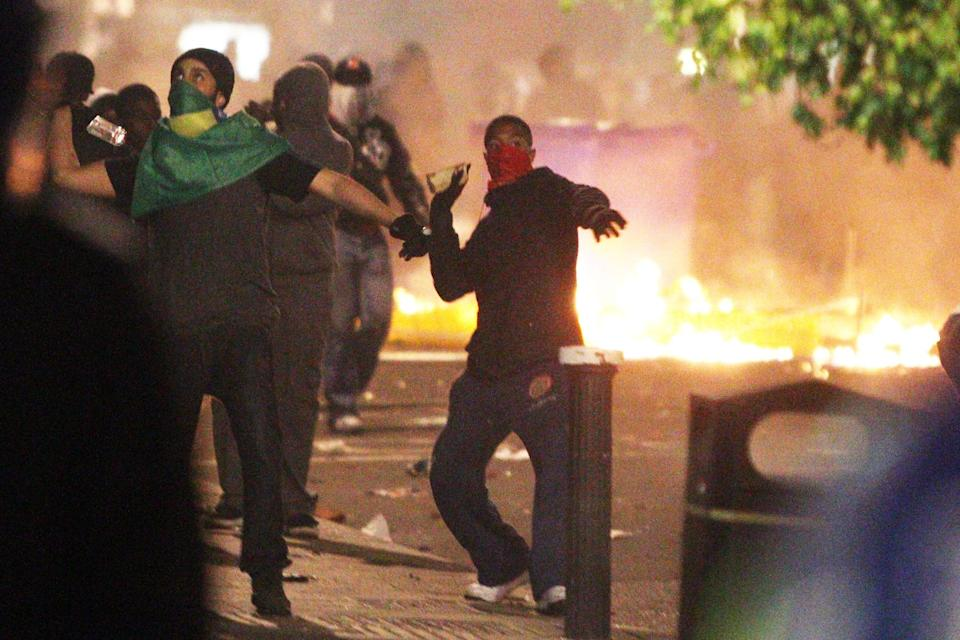 Youths throw objects at riot police during the first night of the summer riots, in Tottenham, London. (PA)