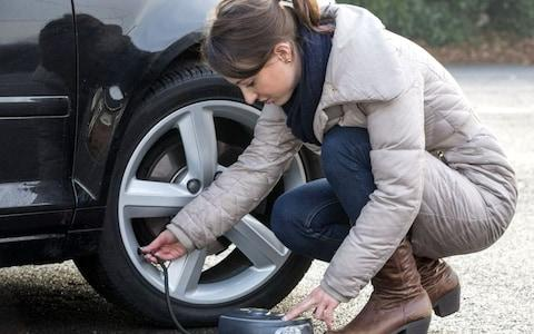 May0052013. Daily Telegraph. Winter Mainteinance Checks for DT Motoring. Rebecca Jackson checks her car for winter. Picture shows, Rebecca Jackson inflating a tyre. Picture date 12/12/2013