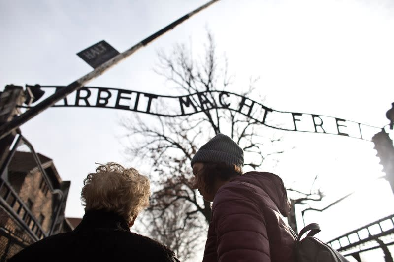 "Jona Laks, survivor of Dr. Josef Mengele's twins experimentsand her granddaughter, Lee Aldar stand next to the gate with the slogan ""Arbeit macht frei"" (""Work sets you free"") as they start their visit at the Auschwitz death camp in Oswiecim"