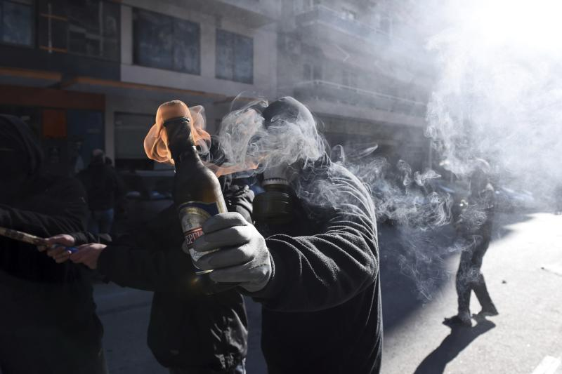 A hooded youth prepares to throw a petrol bomb at riot police in the northern Greek city of Thessaloniki, on Thursday, Dec. 6, 2018 during a rally commemorating the killing of a 15-year old student back in 2008. School and university students marched in various towns of the country to mark the tenth anniversary of a fatal police shooting of a teenager in Athens that sparked the worst rioting Greece had seen in decades. (AP Photo/Giannis Papanikos)