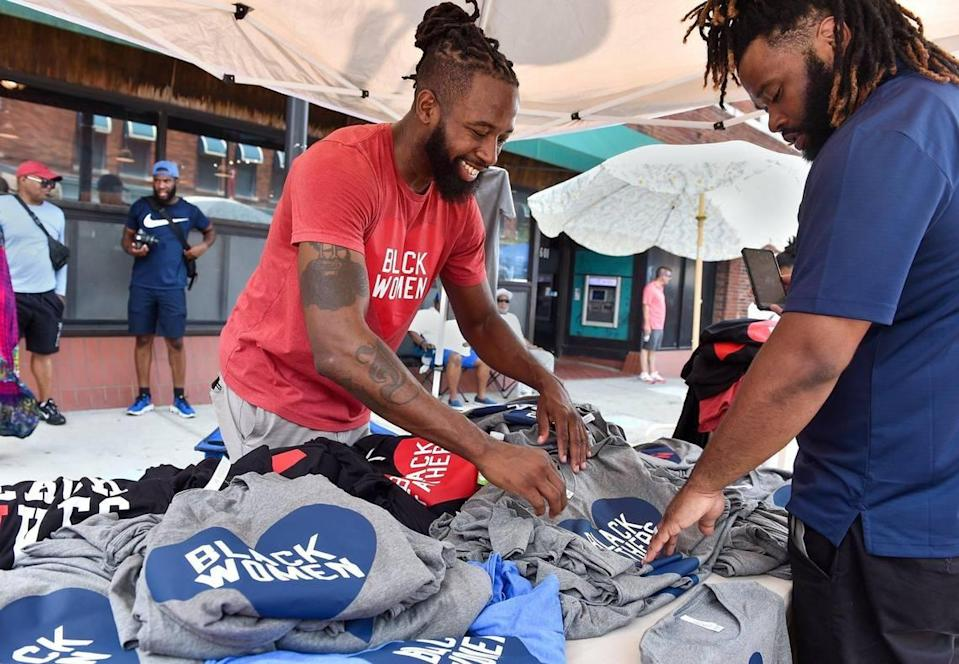 Jeff Harris with Heart Black Lives, shows customer Cameron Gentry of Kansas City some of the t-shirts for sale at Kansas City's Juneteenth Heritage Festival in the 18th and Vine Jazz District Saturday, June 19, 2021. Gentry purchased two t-shirts that say Black Fathers.