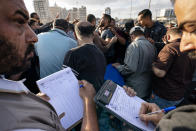Recorders take down winning bids on fish lots as the day's catch is sold at auction after a limited number of boats were allowed to return to the sea following a cease-fire reached after an 11-day war between Hamas and Israel, in Gaza City, Sunday, May 23, 2021. (AP Photo/John Minchillo)