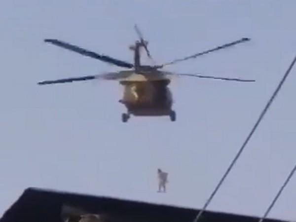 Screengrab of a video showing the Taliban flying a US Black Hawk chopper with a body hanging from it.