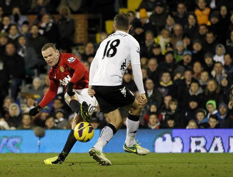 Manchester United's striker Wayne Rooney (L) scores past Fulham's defender Aaron Hughes during an English Premier League football match at Craven Cottage Stadium in London, England, on February 2, 2013. Manchester United overcame a floodlight failure to win 1-0 at Fulham through a late Rooney goal on Saturday as Alex Ferguson's side went 10 points clear at the top of the Premier League