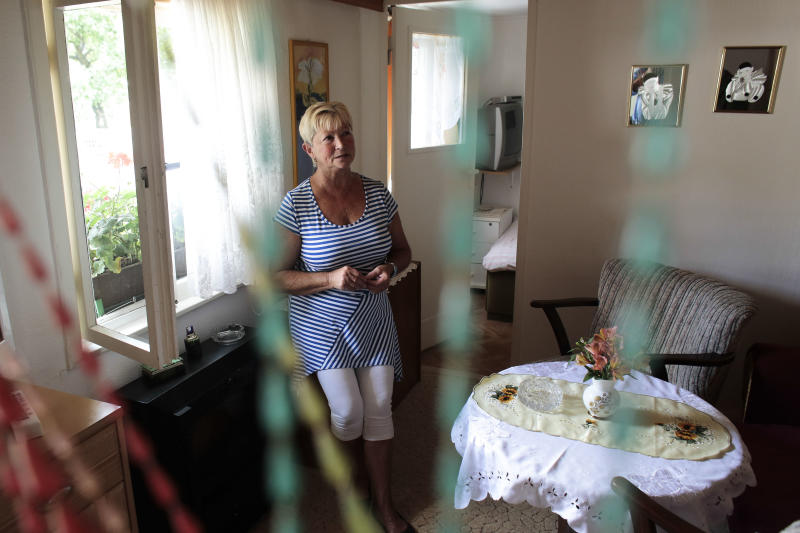 In this Aug. 29, 2013 photo, 70-year-old Christel Paweski, who worked in a hospital and a nursing home before retiring six years ago, stands near a window during an interview with The Associated Press in Berlin. Paweski's plight and that of millions of other Germans living below or close to the poverty line burst onto the campaign for the Sept. 22 national election after she tearfully confronted Chancellor Angela Merkel on national television, asking whether the country's leader had forgotten the growing numbers of retirees and working poor who have missed out on Germany's economic success. (AP Photo/Markus Schreiber)