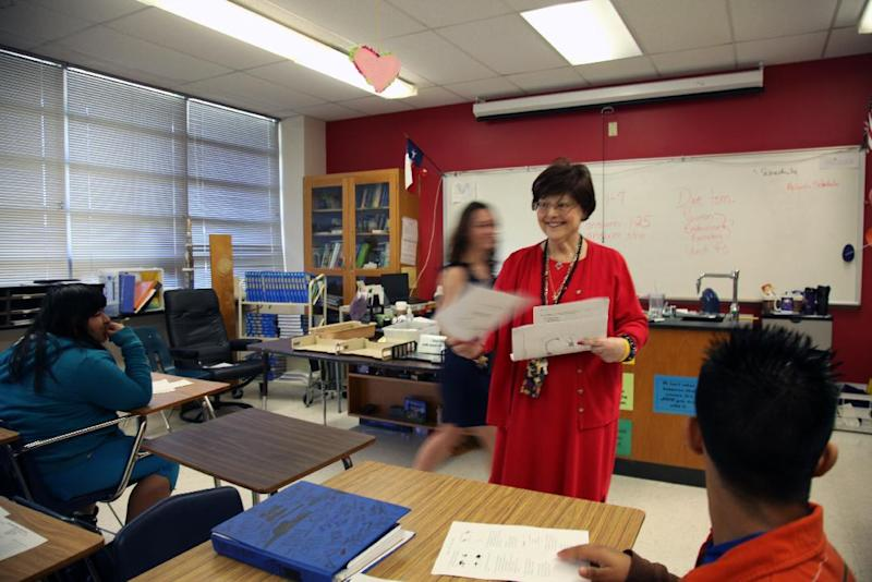In this March 20, 2013 photo, Susan Templer passes out test forms to her science class in Richardson, Texas. Templer was diagnosed with pancreatic cancer in 2011, but has continued teacher through her illness to reach her 25 year service mark. (AP Photo/John L. Mone)