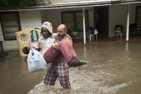 Charles Davidson helps his neighbor Santonio Coleman, 11, from his flooded home in the Kelly Ave. Basin area of Pensacola, Florida, April 30, 2014. REUTERS/Michael Spooneybarger