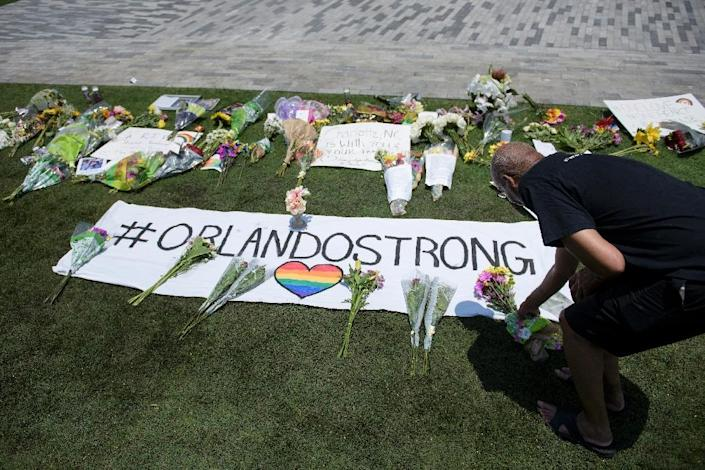Derrick Miller places flowers at a makeshift memorial for the mass shooting victims at the Pulse nightclub on June 13, 2016 in Orlando, Florida (AFP Photo/Brendan Smialowski)