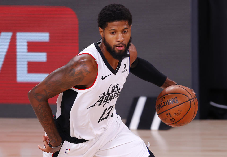 Paul George dribbles the ball while wearing a white Los Angeles Clippers jersey.
