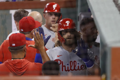 Philadelphia Phillies' Bryce Harper is congratulated in the dugout after hitting a three-run home run against the Boston Red Sox during the sixth inning of a baseball game Tuesday, Aug. 18, 2020, at Fenway Park in Boston. (AP Photo/Winslow Townson)