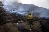 A municipal worker looks as smoke rises after a volcano erupted, near El Paso on the island of La Palma in the Canaries, Spain, Tuesday, Sept. 21, 2021. A dormant volcano on a small Spanish island in the Atlantic Ocean erupted on Sunday, forcing the evacuation of thousands of people. Huge plumes of black-and-white smoke shot out from a volcanic ridge where scientists had been monitoring the accumulation of molten lava below the surface. (AP Photo/Emilio Morenatti)