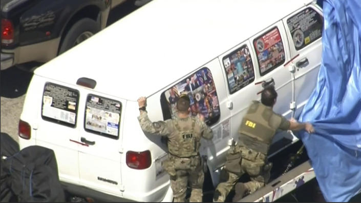 <p>This frame grab from video provided by WPLG-TV shows FBI agents covering a van after the tarp fell off as it was transported from Plantation, Fla., on Friday, Oct. 26, 2018, that federal agents and police officers have been examining in connection with package bombs that were sent to high-profile critics of President Donald Trump. The van has several stickers on the windows, including American flags, decals with logos and text. (Photo: WPLG-TV via AP) </p>