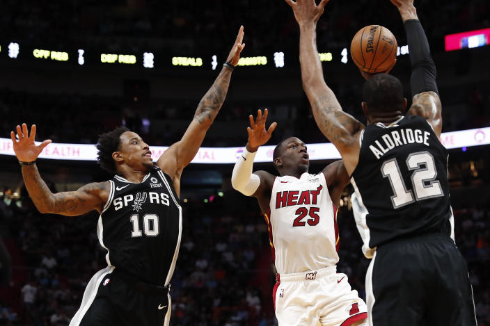 Miami Heat guard Kendrick Nunn shoots the ball against San Antonio Spurs guard DeMar DeRozan and center LaMarcus Aldridge.