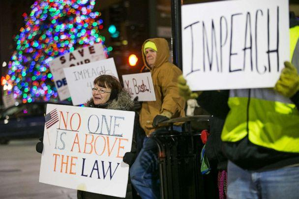PHOTO: Jean Hotopp of Rockford, left, and dozens of other protesters hold signs and chant slogans advocating impeachment of President Donald Trump on Tuesday, Dec. 17, 2019, at the intersection of State Street and Wyman Street in Rockford. (Scott P. Yates/Rockford Register Star via AP)
