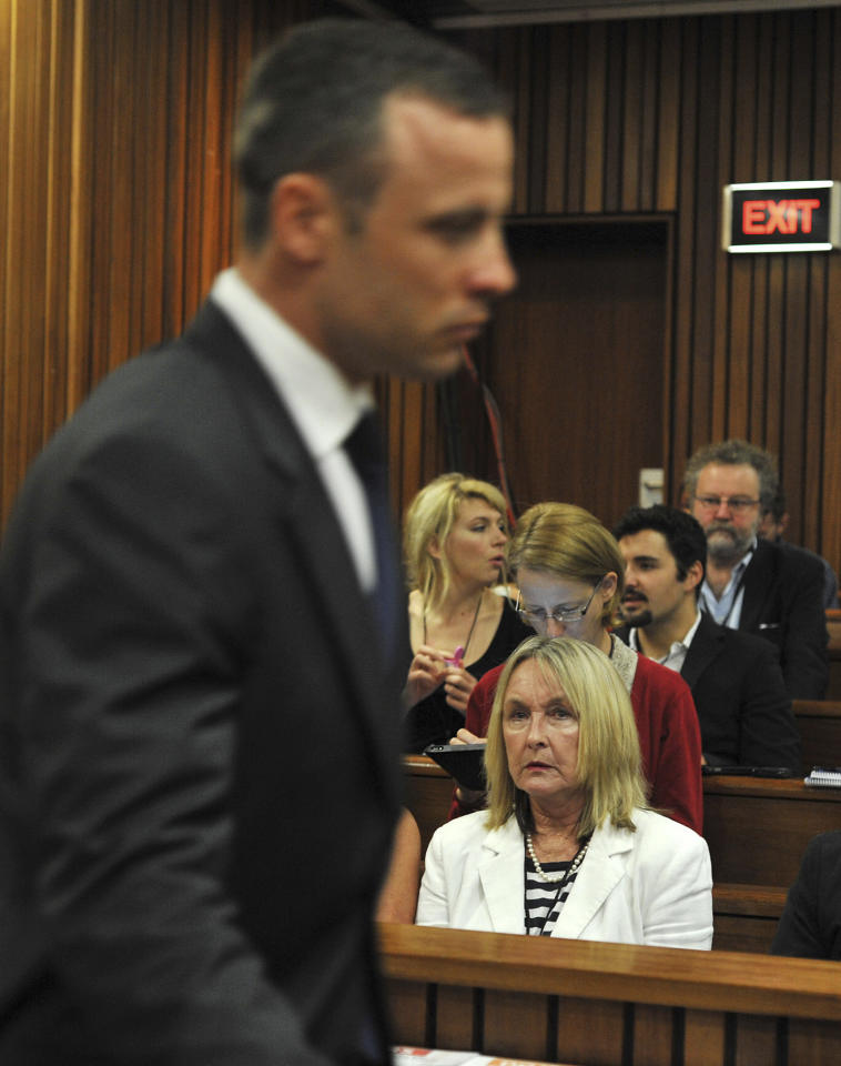 Oscar Pistorius, left, walks past June Steenkamp, right, the mother of the late Reeva Steenkamp, upon his arrival at the high court in Pretoria, South Africa, Monday, March 24, 2014. The trial of Pistorius, who is charged with murder for the shooting death of his girlfriend Reeva Steenkamp on Valentines Day in 2013, is beginning its fourth week. The prosecution has said it will wrap up its case against the double-amputee runner this week after calling four or five more witnesses, beginning Monday. (AP Photo/Ihsaan Haffejee, Pool)