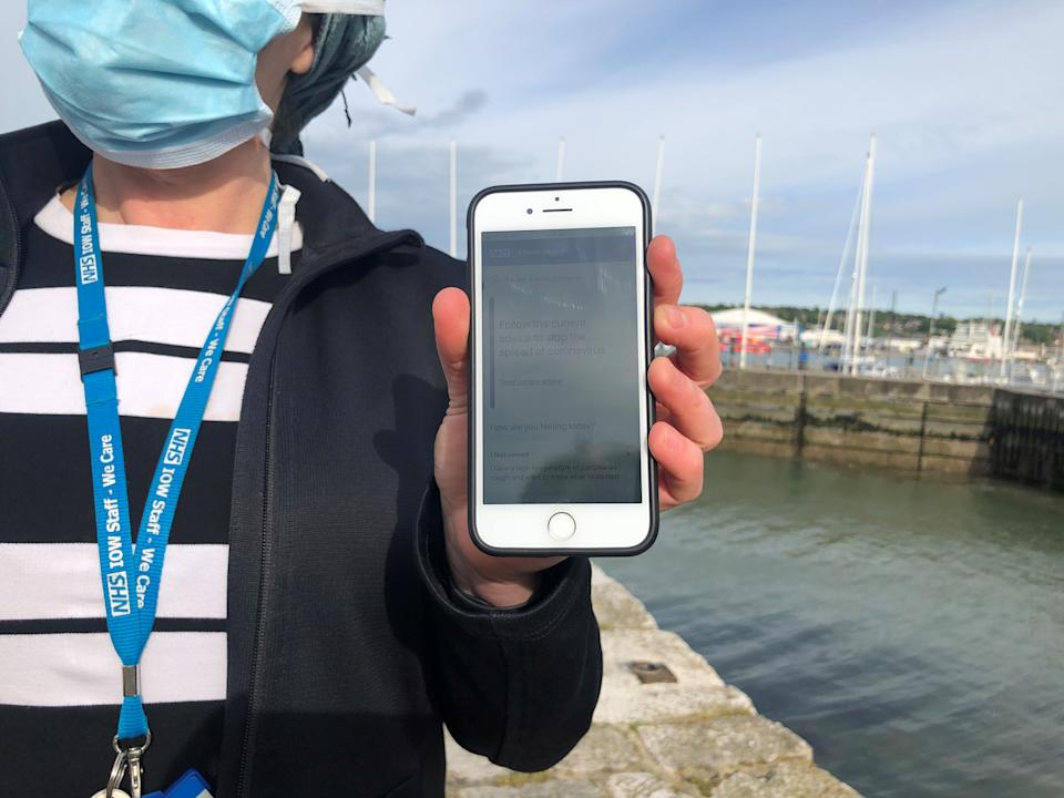 UK National Health Service employee Anni Adams shows a smartphone displaying the new NHS app to trace contacts with people potentially infected with the coronavirus disease (COVID-19) being trialled on Isle of Wight, Britain, May 5, 2020. Picture taken May 5, 2020. REUTERS/Isla Binnie