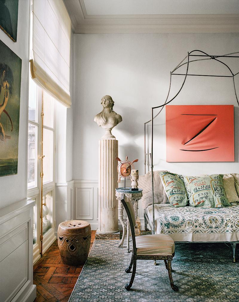 In the guest bedroom, a Maurizio Cattelan painting hangs over an antique French bed.