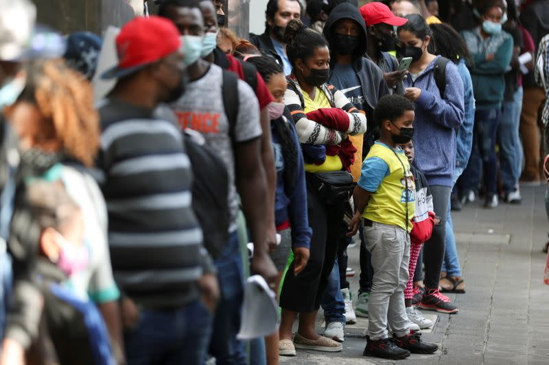 Migrants from Haiti and Central America line up to regularize their migratory situation outside of the Mexican Commission for Aid to Refugees (COMAR), in Mexico City