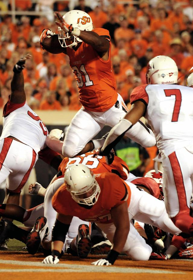 Oklahoma State running back Jeremy Smith, top center, jumps for a touchdown over the back of lineman Calvin Barnett, bottom, while Lamar defensive back Courtlin Thompson, right, watches during the first half of an NCAA college football game in Stillwater, Okla., Saturday, Sept. 14, 2012. (AP Photo/Brody Schmidt)