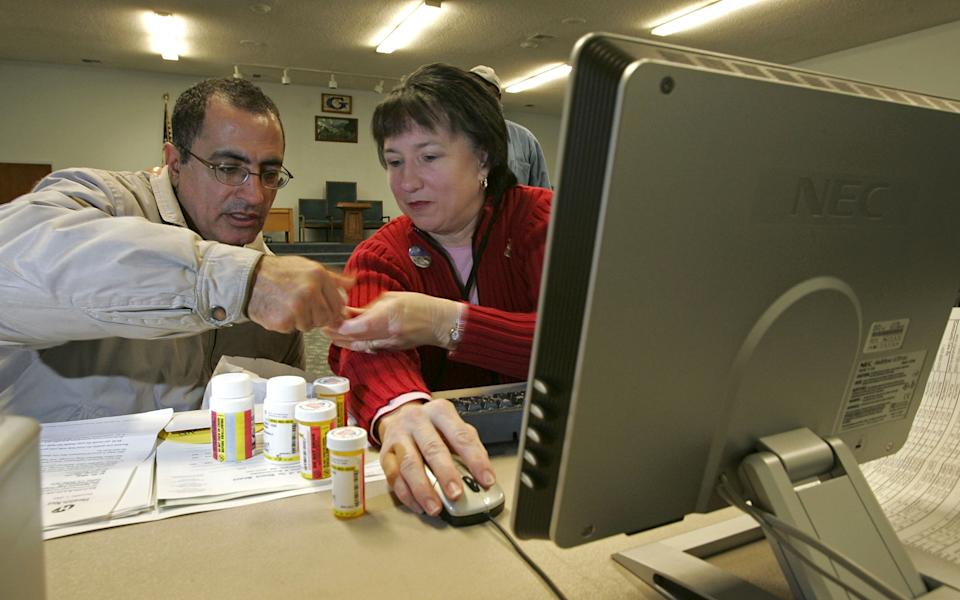 PLEASANTON, CA - DECEMBER 19:  Volunteer Rebecca Cox (R) helps a man log perscription drug information as he registers his parents for the new Medicare drug prescription program during a Medicare enrollment event December 19, 2005 in Pleasanton, California. Open enrollment for the new program began November 15 and will continue through May 15, 2006.  (Photo by Justin Sullivan/Getty Images)