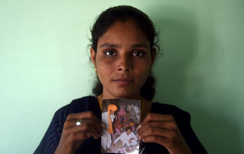 University student Santadevi Meghwal, a victim of child marriage, poses with a photograph of her wedding ceremony in Jodhpur (AFP Photo/Money Sharma)