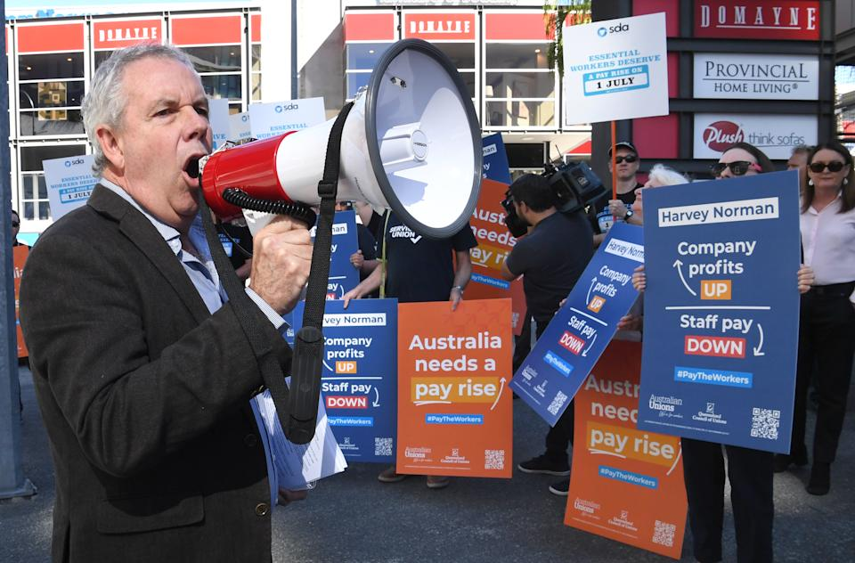 Michael Clifford (left), General Secretary of the Queensland Council of Unions is seen addressing workers as they protest about pay outside Harvey Norman Fortitude Valley in Brisbane. Source: AAP