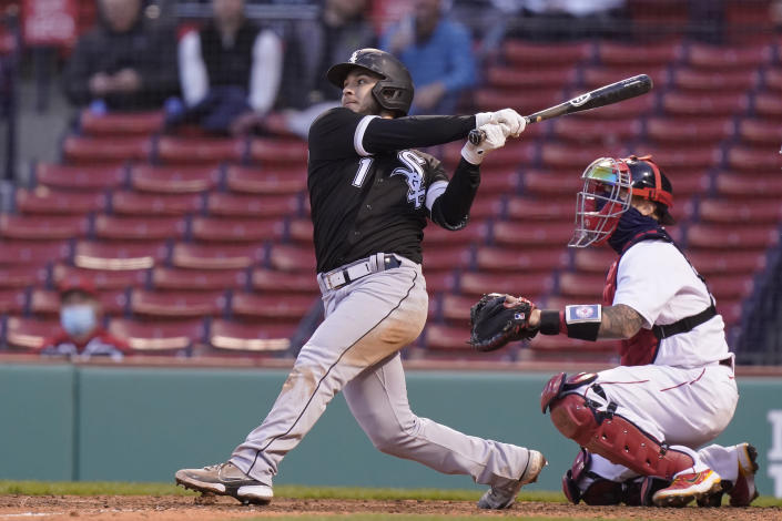 Chicago White Sox's Nick Madrigal, left, hits a sacrifice fly, allowing teammate Leury Garcia to score, as Boston Red Sox's Christian Vazquez, right, looks on in the sixth inning of a baseball game, Sunday, April 18, 2021, in Boston. The game is the second of a doubleheader Sunday. (AP Photo/Steven Senne)