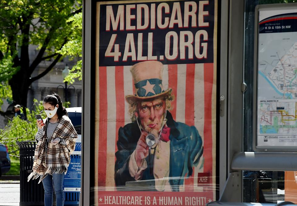 A pedestrian wearing a protective mask checks her phone near a Medicare for All bus stop billboard in Washington, DC, on April 22, 2020. (Photo by Olivier DOULIERY / AFP) (Photo by OLIVIER DOULIERY/AFP via Getty Images)
