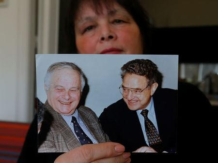 Vasarhelyi, a Hungarian sociologist and opposition activist, holds a picture of billionaire philanthropist George Soros with her late father Miklos Vasarhelyi, who led the Soros Foundation in Hungary in the 1980s and 1990s, in Budapest