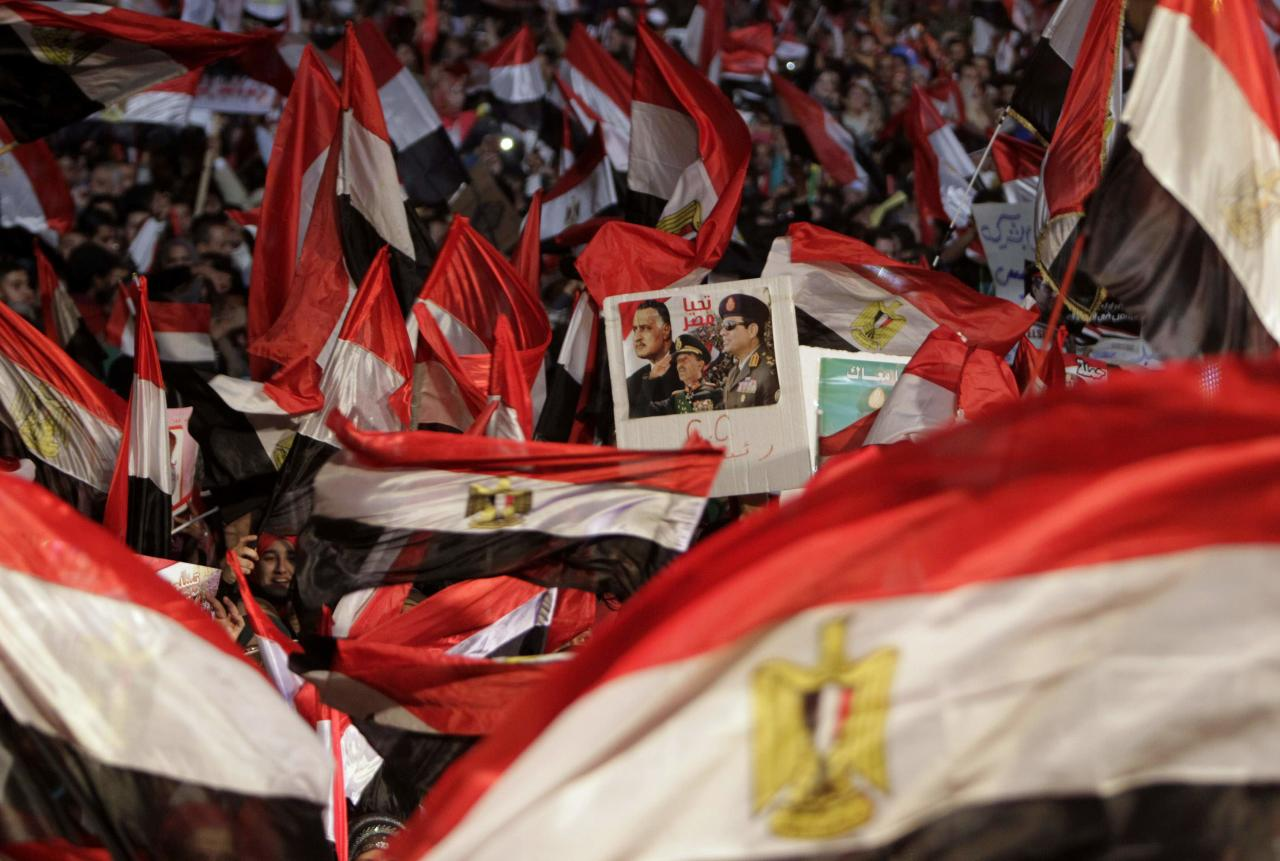Supporters of Egypt's army chief General Abdel Fattah al-Sisi hold a poster of Sisi in Tahrir square in Cairo