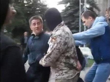 Horlivka city deputy Volodymyr Rybak is manhandled by several men outside a city hall building in Horlivka