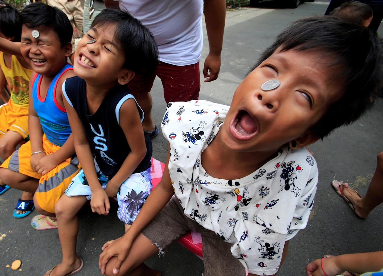 Boys use their faces and tongues, to move a coin from their foreheads into their mouths, at a town fiesta parlour game, in celebration of the patron saint Santa Rita de Cascia in Baclaran, Paranaque City, Metro Manila, Philippines May 20, 2018. REUTERS/Romeo Ranoco