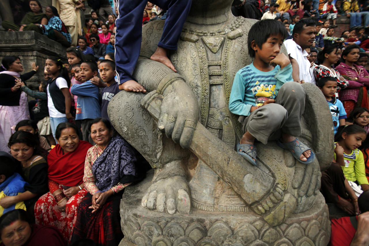 Nepalese devotees watch a procession during the Bisket Jatra Hindu festival celebrations on the outskirts of Katmandu, Nepal, Monday, April 9, 2012. During this festival, also regarded as a New Year festival, images of the god Bhairava and his female counterpart Bhadrakali are enshrined in two large chariots and pulled to an open square after which rituals and festivities are carried out. (AP Photo/Niranjan Shrestha)