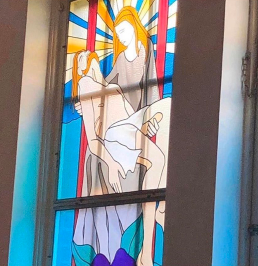 A photo of a stained-glass church window with Virgin Mary holding Jesus by a peculiar phallic object.