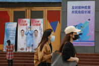 """A medical worker stands near billboards portraying renowned Chinese Dr. Zhong Nanshan with the words """"Vaccine China Made"""" at a vaccination site in Beijing on Friday, April 9, 2021. China's success at controlling the coronavirus outbreak has resulted in a population that has seemed almost reluctant to get vaccinated. Now, it is accelerating its inoculation campaign by offering incentives — free eggs, store coupons and discounts on groceries and merchandise — to those getting a shot. (AP Photo/Ng Han Guan)"""