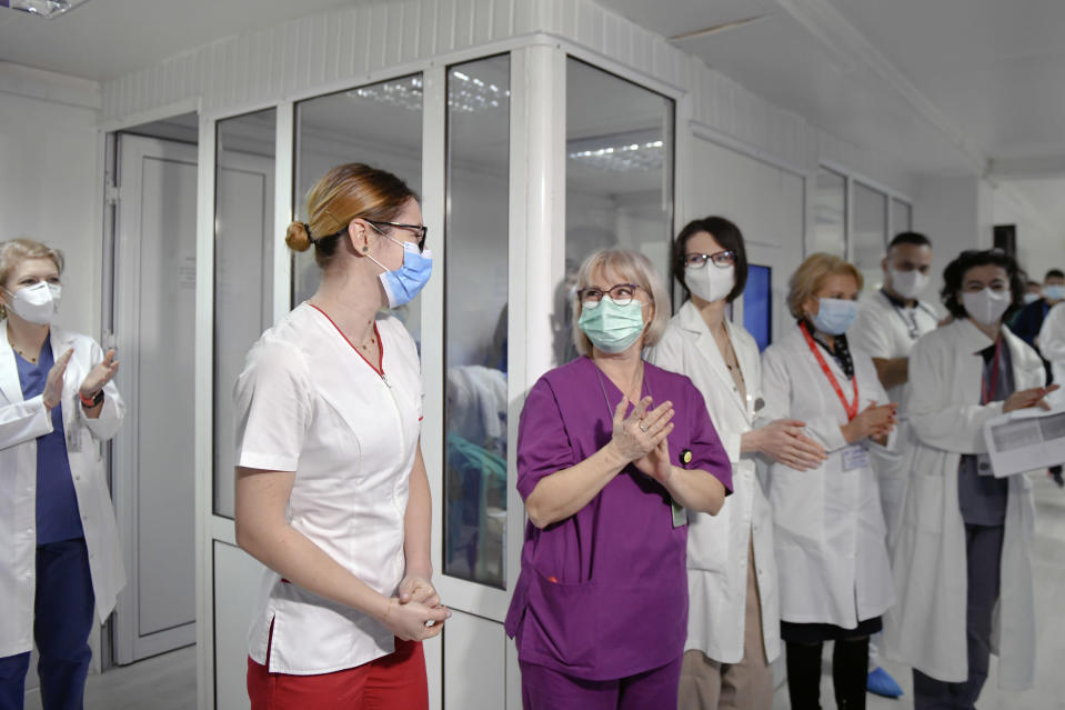Mihaela Anghel, second from left, a Romanian nurse, gets a round of applause from colleagues after getting the first COVID-19 vaccine administered in the country in Bucharest, Romania, Sunday, Dec. 27, 2020. Anghel is the nurse who registered and processed Romania's first official COVID-19 patient, on Feb. 27 2020. (AP Photo/Andreea Alexandru)